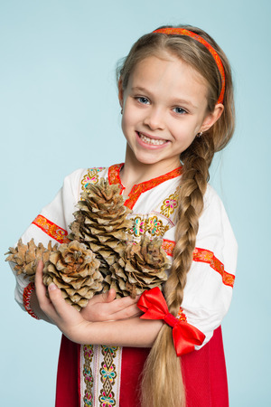seven years: Beautiful girl in a traditional Russian folk costume holding pine cones. Girl seven years. Stock Photo
