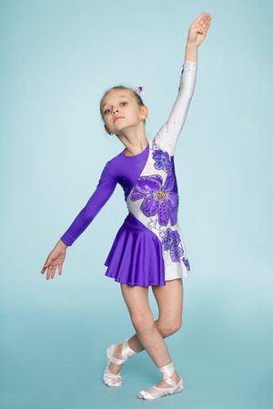 seven years: Dancing little girl seven years on a blue background. Stock Photo