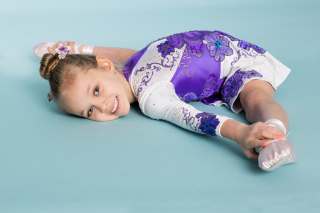 seven years: Little girl does the split on a blue background. Girl seven years. Stock Photo