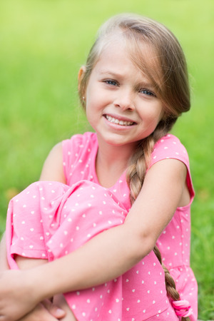 seven years: Portrait of a cute young girl sitting on the grass in the park. Girl seven years. Stock Photo