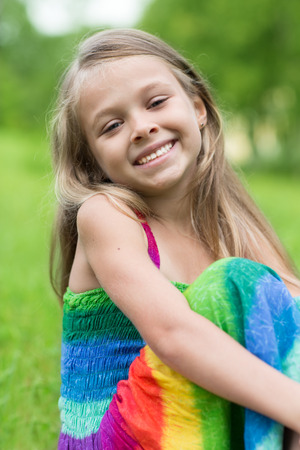 seven years: Little happy girl sitting on the grass. Girl seven years.