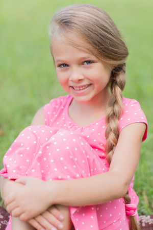 Portrait of a cute girl with a lovely smile sitting on the grass. Girl seven years. photo
