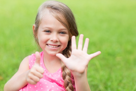 seven years: Smiling girl showing thumb up. Girl seven years.