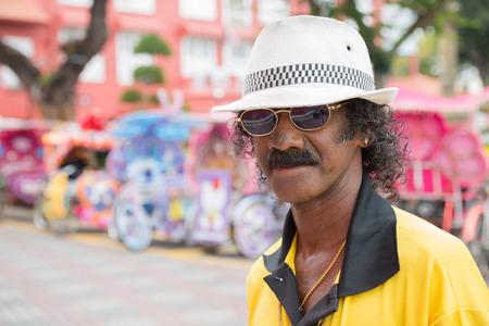 unusually: MALACCA, MALAYSIA - CIRCA JANUARY, 2015: Portrait of an unusually flamboyant Malay man in a hat, met on the street in Malacca.