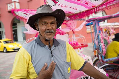 unusually: MALACCA, MALAYSIA - CIRCA JANUARY, 2015: Portrait of an unusually flamboyant Malay rickshaw man in a hat, met on the street in Malacca. Editorial
