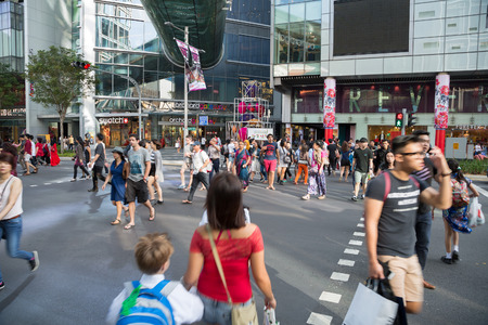 enclave: SINGAPORE - CIRCA FEBRUARY, 2015: People on a pedestrian crossing on Orchard Road. Orchard Road it is a huge tourist attraction, most popular shopping enclave in the city-state.