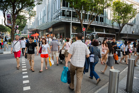crossing street: SINGAPORE - CIRCA FEBRUARY, 2015: People on a pedestrian crossing on Orchard Road. Orchard Road it is a huge tourist attraction, most popular shopping enclave in the city-state.