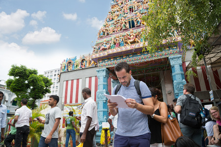 tekka: SINGAPORE - FEBRUARY 19, 2015: European tourist on background indian Hinduism temple in Little India. Little India or the Indian quarter, a very popular area with tourists visiting Singapore.