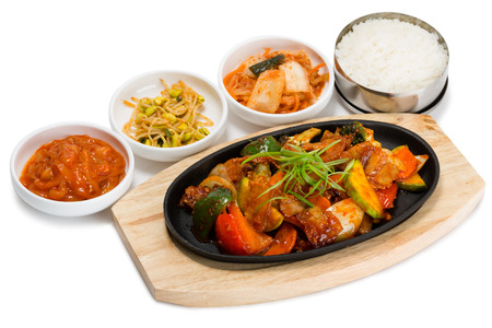 Roasted meat with vegetables in a skillet with rice and spicy salad. From a series of Food Korean cuisine. photo