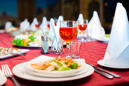 holiday food: Festively served banquet table with glasses and salads. Stock Photo