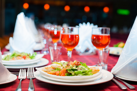 served: Served banquet table with glasses and salads. Stock Photo