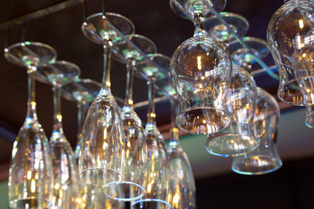 bocal: Wine glasses hanging above the bar rack in the restaurant. Stock Photo