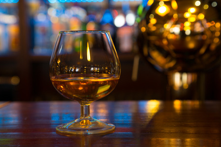 alcoholic drink: Glass with an alcoholic drink is on the bar rack Stock Photo
