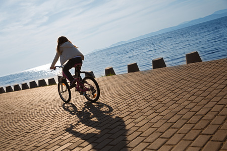 young girl: Girl rides a bike on the promenade by the sea at sunset. Focus on the pavement. On image superimposed filter Color Lookup.