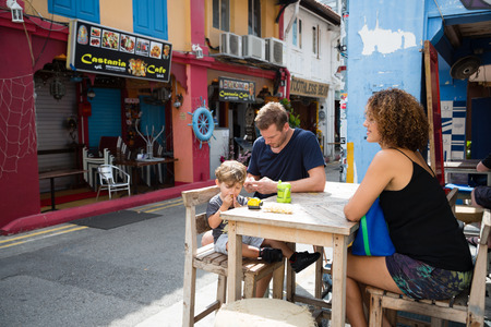 SINGAPORE - CIRCA FEBRUARY, 2015: Happy family in the Arab quarter Kampong Glam. Arab Quarter is the oldest historic shopping district of Singapore, is popular for visiting tourists. Sajtókép