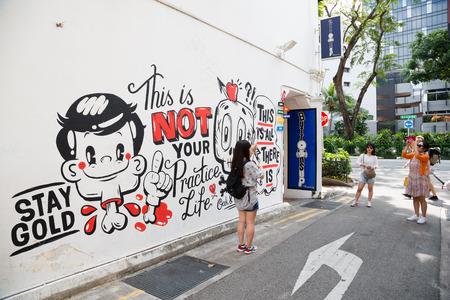neighbourhood: SINGAPORE - CIRCA FEBRUARY, 2015: Graffiti on the walls of old buildings Haji Lane. Haji Lane is the Kampong Glam (Arab Quarter) neighbourhood famous for its cafes, restaurants and shops.