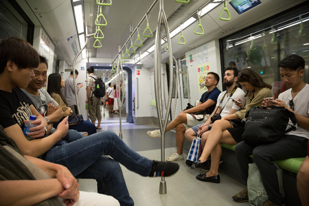 encompasses: SINGAPORE - CIRCA FEBRUARY, 2015: Passengers traveling on the subway in Singapore. The MRT network encompasses 152.9 kilometres of route, with 113 stations in operation. Editorial