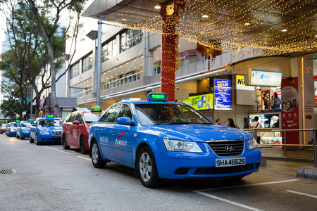 medios de transporte: SINGAPUR - alrededor de febrero de 2015: Taxi en Orchard Road, en la ciudad de Singapur. Singapur más de 25 mil vehículos que participan en karting pasajeros, taxi es una forma importante y popular de transporte público. Editorial