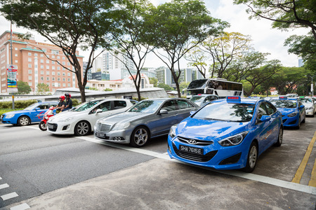 carting: SINGAPORE - CIRCA FEBRUARY, 2015: Taxis in the city Singapore. Singapore more than 25 thousand cars involved in carting passengers, taxi is an important and popular form of public transport.