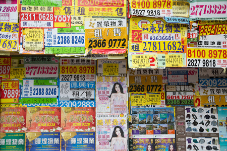 classifieds: HONG KONG - CIRCA FEBRUARY, 2015: Advertisements on the wall in the bustling district of Hong Kong.