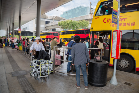 tourists stop: HONG KONG - CIRCA FEBRUARY, 2015: Arrived people stand in line at the bus stop International Airport Chek Lap Kok. Thousands of tourists arriving aircraft use the services of buses.