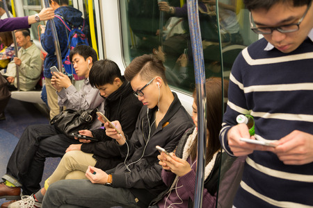 smartphone: HONG KONG - CIRCA FEBRUARY, 2015: People traveling in the subway and actively use smartphones. Metro aka MRT is the most popular form of public transport in Hong Kong.