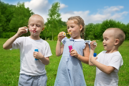 inflate: Happy brothers and sister inflate soap bubbles outdoors in park Stock Photo