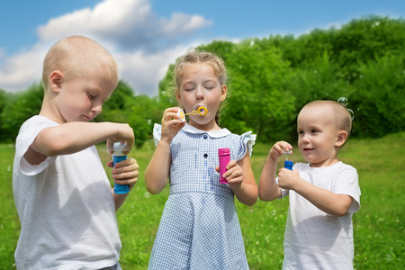 inflate: Happy brother and sister inflate soap bubbles outdoors. Stock Photo