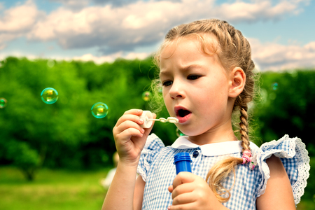 play the old park: Girl blowing soap bubbles in summer park. Image with Instagram-like filter.