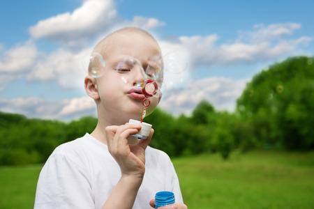 burbujas de jabon: Boy se infla burbujas de jabón en el parque. Foto de archivo