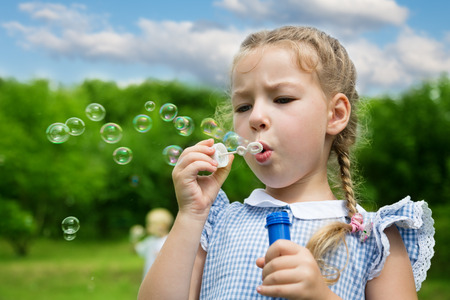 girl blowing: Girl blowing soap bubbles in summer park Stock Photo