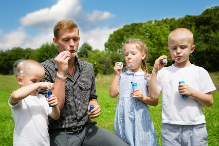 teaches: Elder brother teaches the younger brothers and sister blowing bubbles