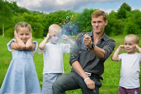 firecracker: Older brother shoots of the firecracker on a family holiday. Stock Photo