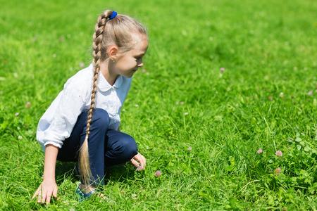 guadaña: Chica con una guadaña en la hierba atrapa saltamontes