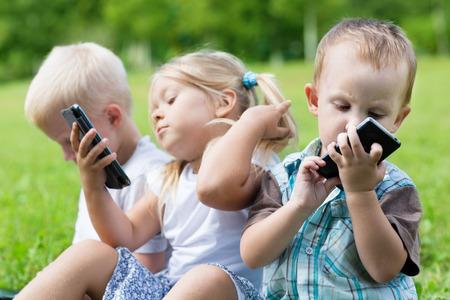 mujer hijos: Niños felices que usan teléfonos inteligentes que se sientan en la hierba. Hermanos y hermana.