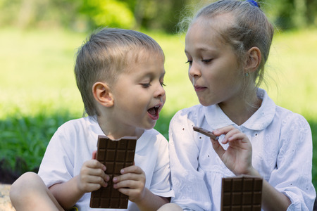 children eating: Brother and sister having fun eating chocolate outdoors. Summer day in park. Stock Photo
