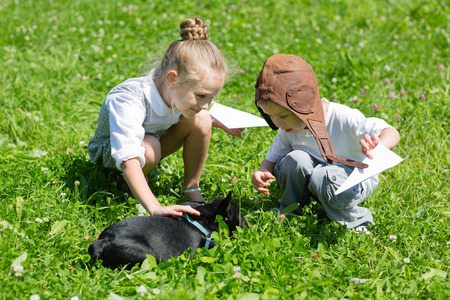 childen: Joyful kids playing with the dog (French bulldog) on the grass. Brother and sister. Stock Photo