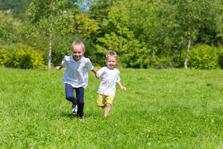 jeune fille: Enfants joyeux Happy fonctionnant sur l'herbe dans le parc de l'automne Banque d'images