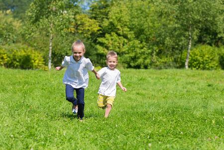 familias jovenes: Ni�os alegres felices que se ejecutan en la hierba en el parque de oto�o