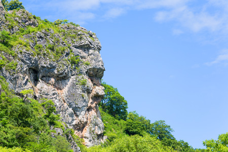 allocated: Natural cliff in the shape of a human head allocated to the mountain range. Far East, Russia.