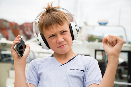 teen boy face: Boy stylish headphones listening to music from your smartphone Stock Photo