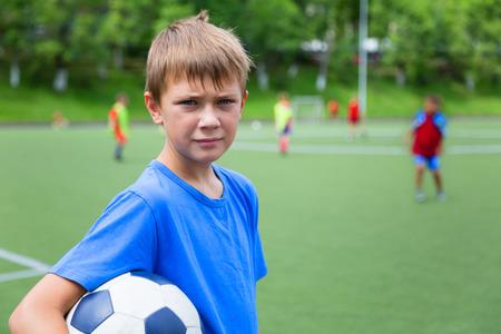 footballer: Boy footballer with a ball in a football stadium.
