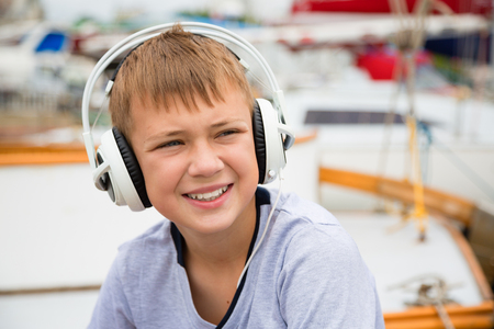 Boy with headphones on the background of yachts. photo