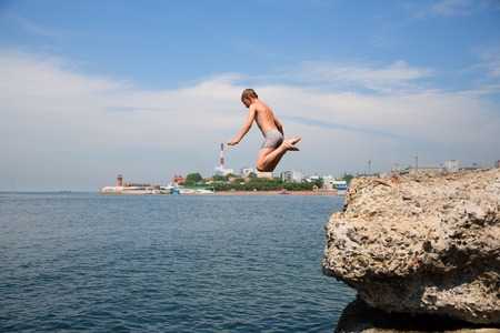 Boy jumping into the sea from the old pier. Embankment in Vladivostok, Russia. photo
