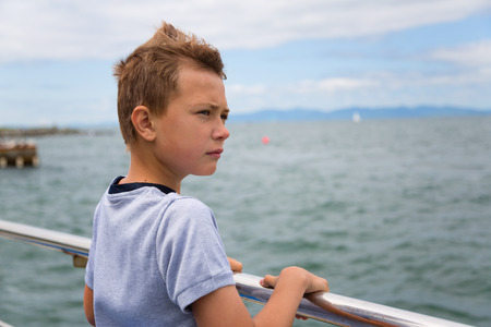Portrait of a dreaming boy on background of the sea photo