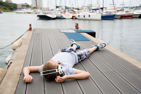 Boy with headphones lying on the mooring and listening to music photo