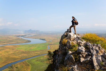 Hiker man climbed a mountain and admire nature. Autumn morning.