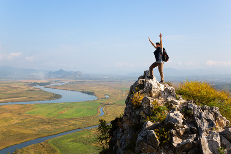 raises: Hiker raises his arms up and screaming with delight. Autumn day.