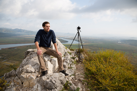 mountaintop: Portrait dreaming photographer sits on a mountaintop. Stock Photo
