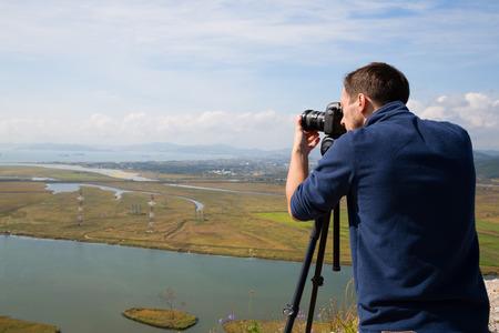 panoramas: Photographer on top of the mountain to shoot panoramas of the Gulf Nakhodka (old name of the Gulf of America) and the city of Nakhodka. Far East, Primorsky Krai, Russia.